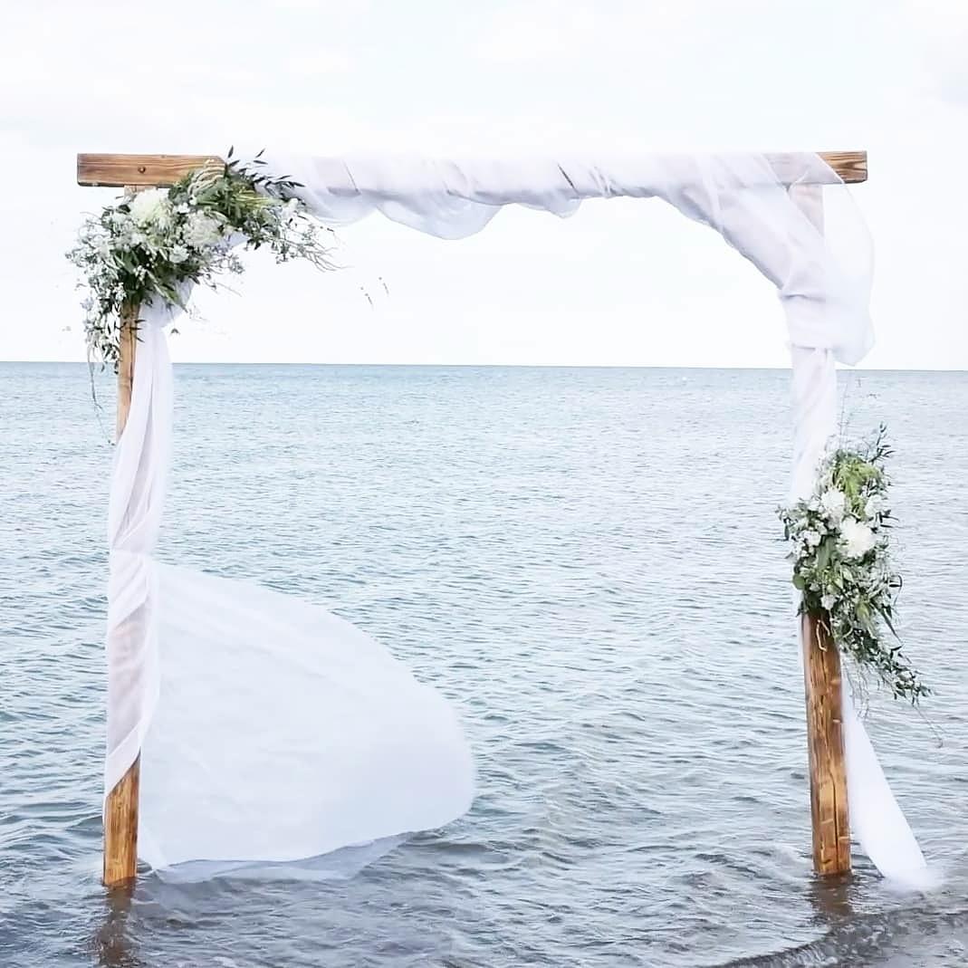 Traubogen aus Holz mit Organzaschsal und Blumengestecken stehend im Wasser kann gemietet werden im Dekoverleih schön anders bei Kiel