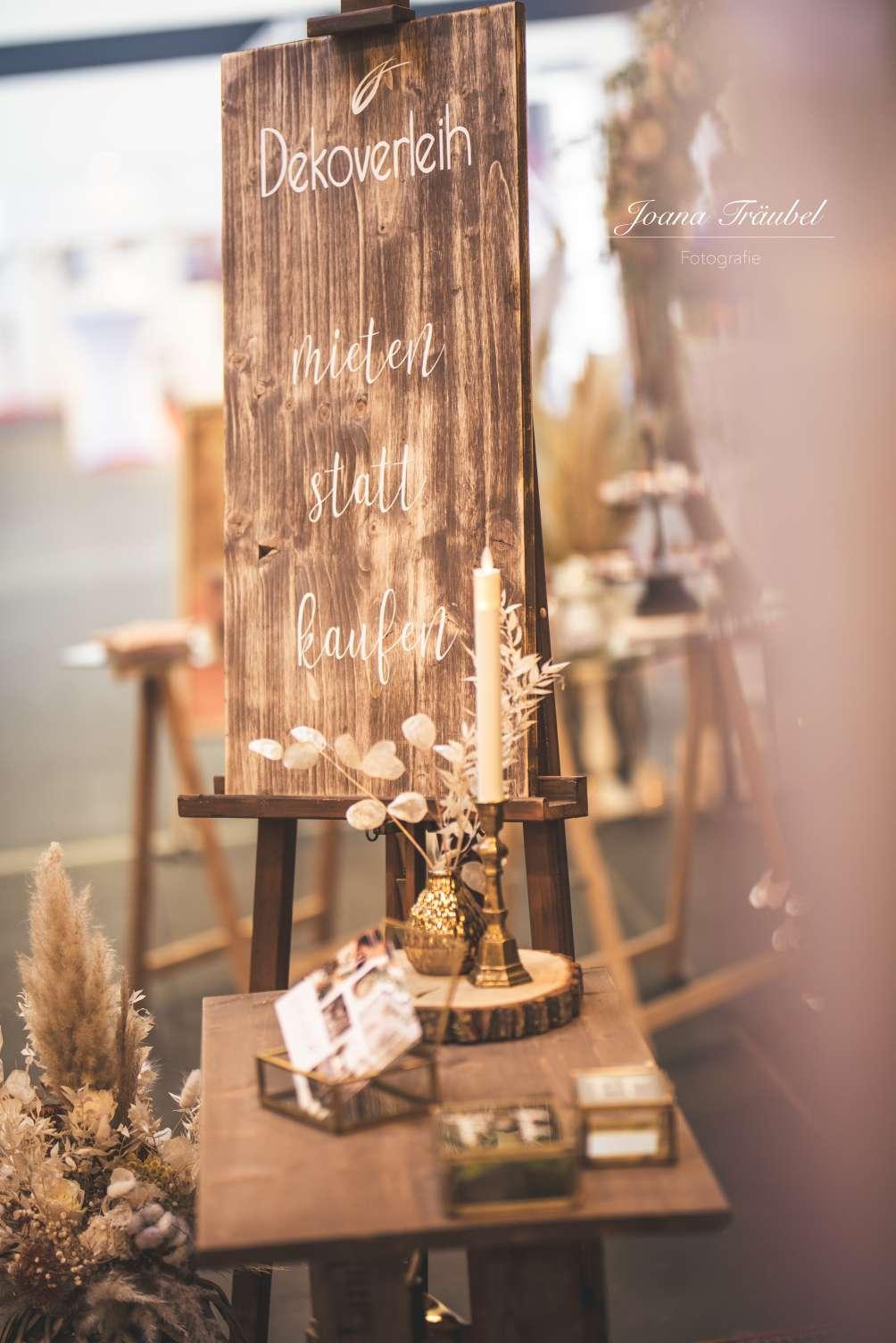 Holzschild mit der Aufschrift Dekoverleih mieten statt kaufen stehend in einer Staffelei aus Holz aufgenommen auf der Hochzeitsmesse Herz an Herz in Neumünster am Stand vom Dekoverleih schön anders bei Kiel dort kann man Deko für eine Hochzeit mieten