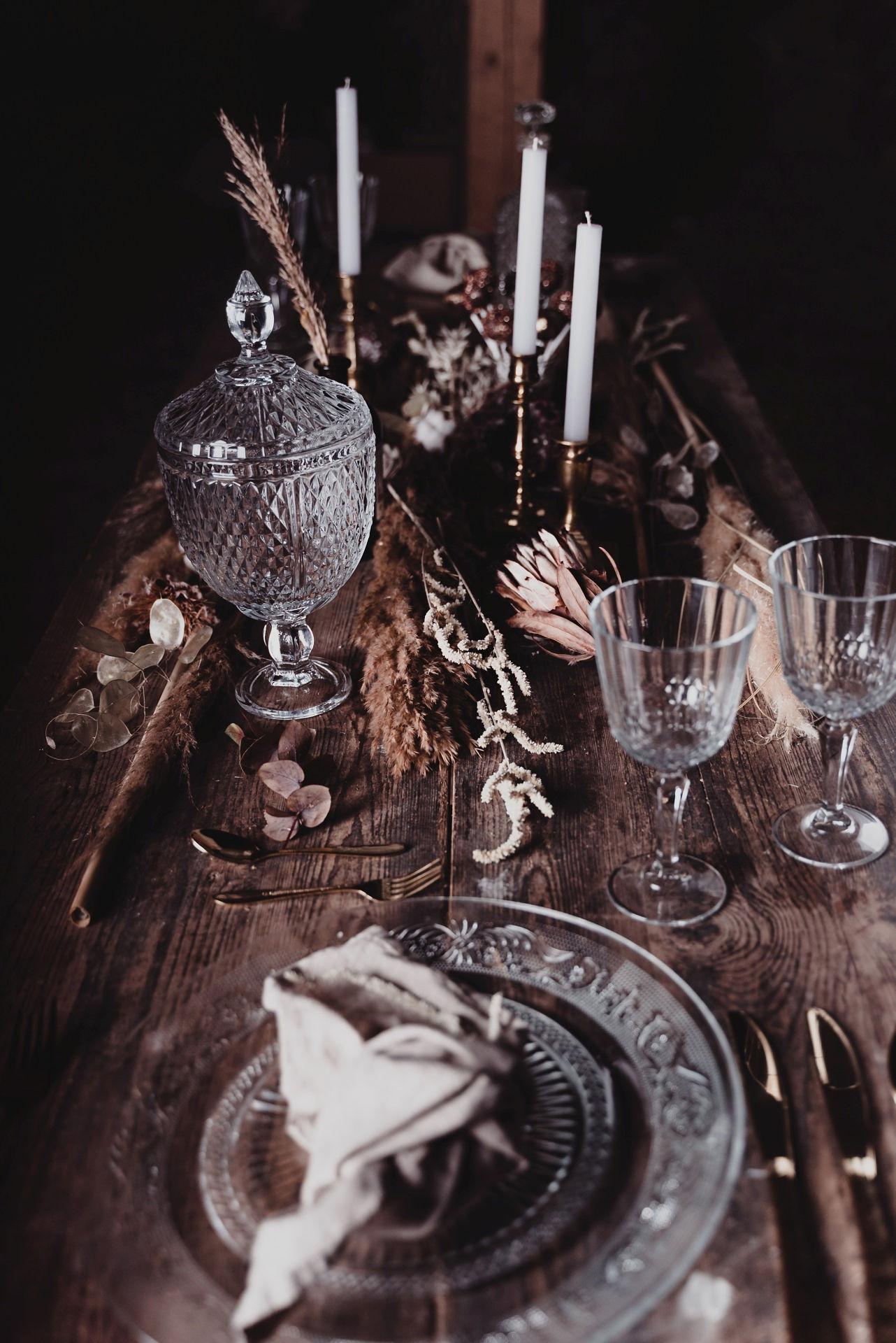 Tischdekoration rustikal auf einem Holztisch mit goldenem Besteck und goldenen Kerzenständern