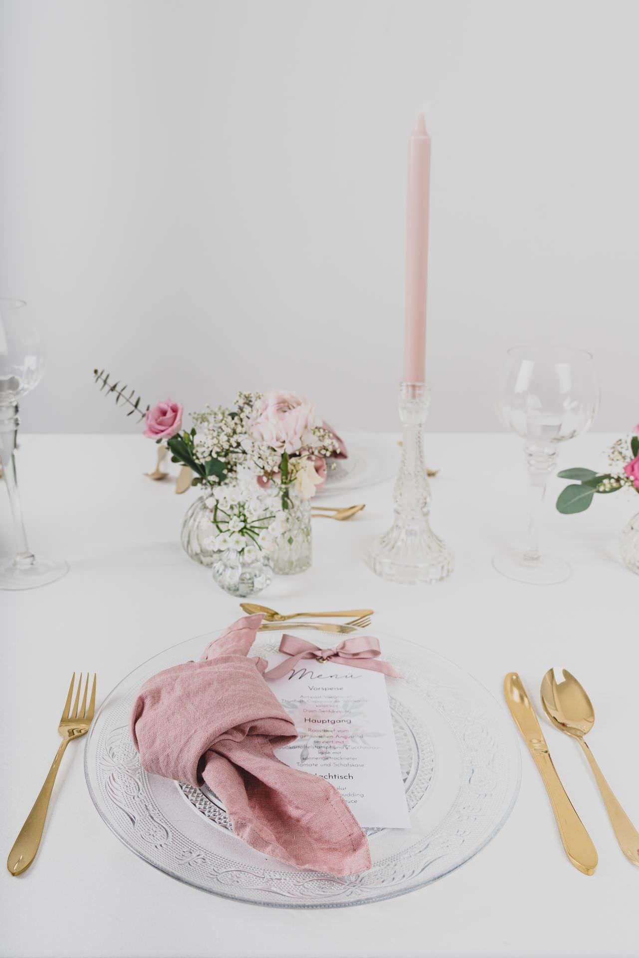 Tischdekoration mit goldenem Besteck Platzteller aus Glas mit Ornamenten und einer rosanen Serviette aus Leinen im Hintergrund weitere Deko aus Glas